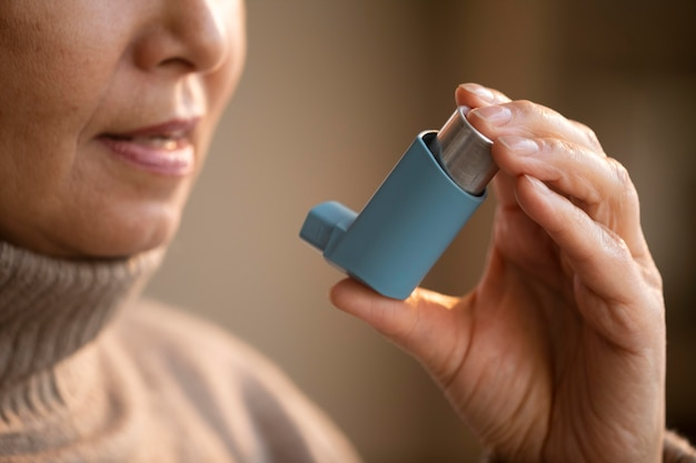Ältere frau, die asthmainhalator hält