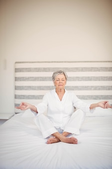 Ältere frau, die auf bett im schlafzimmer meditiert