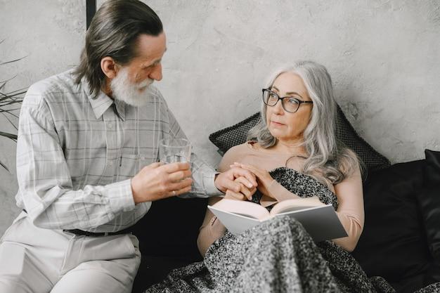 Ältere frau, die auf dem bett liegt und pillen mit fürsorglichem ehemann nimmt. krankheit, quarantäne.