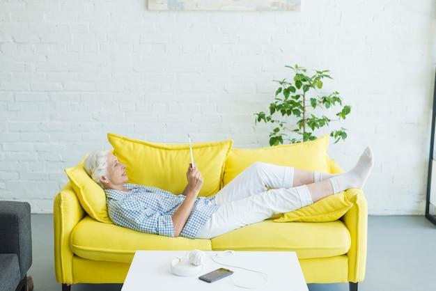 Ältere frau, die auf dem gelben sofa betrachtet digitale tablette liegt