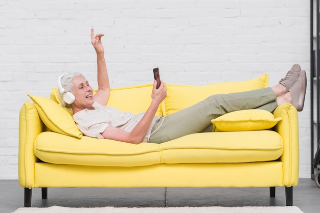 Ältere frau, die auf dem gelben sofa genießt die musik auf mobile durch kopfhörer liegt