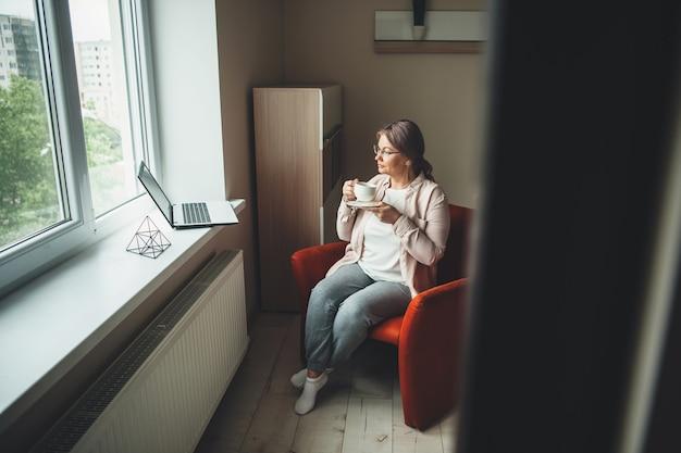 Ältere frau, die auf dem sessel sitzt und tee trinkt, während sie etwas am laptop beobachtet