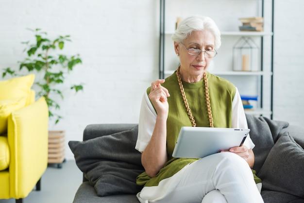 Ältere frau, die auf dem sofa betrachtet digitale tablette sitzt