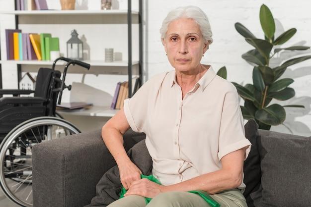 Ältere frau, die auf dem sofa hält grünes ausdehnungsband sitzt