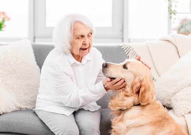 Ältere frau, die auf dem sofa sitzt und golden retriever-hund zu hause streichelt