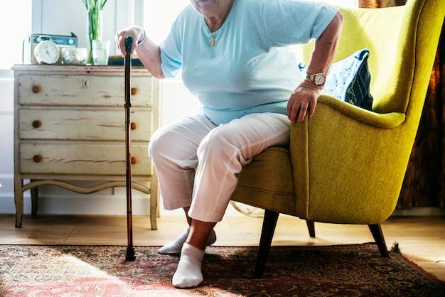 Ältere frau, die auf dem stuhl sitzt