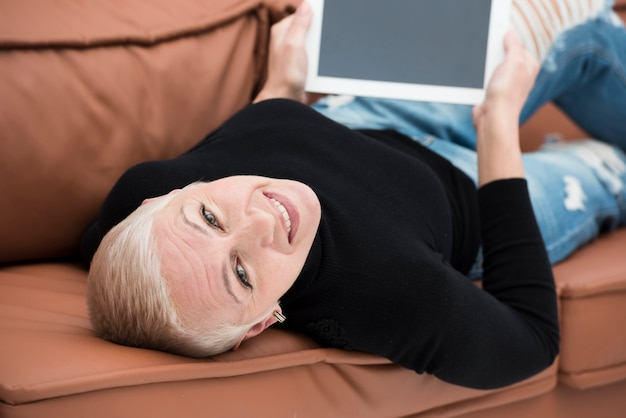 Ältere frau, die auf der couch mit tablette lächelt und sich entspannt
