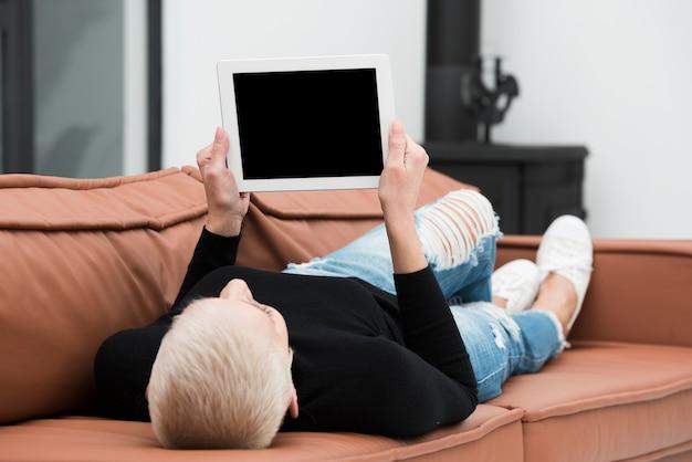 Ältere frau, die auf der couch sich entspannt und tablette hält