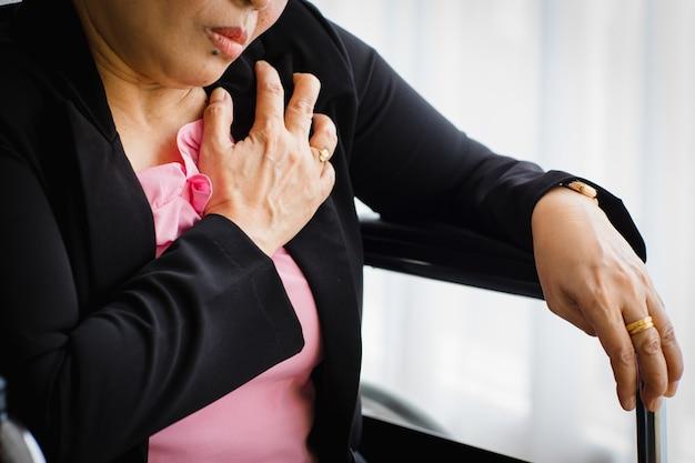 Ältere frau, die auf einem rollstuhl sitzt und an einem plötzlichen herzinfarkt leidet und die brust hält. konzept der notfallversorgung und von herz-lungen-wiederbelebung, herzproblemen betroffen.