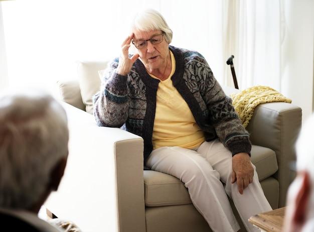 Ältere frau, die auf einem sofa sitzt
