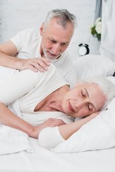 Ältere frau, die auf einem weißen bett schläft