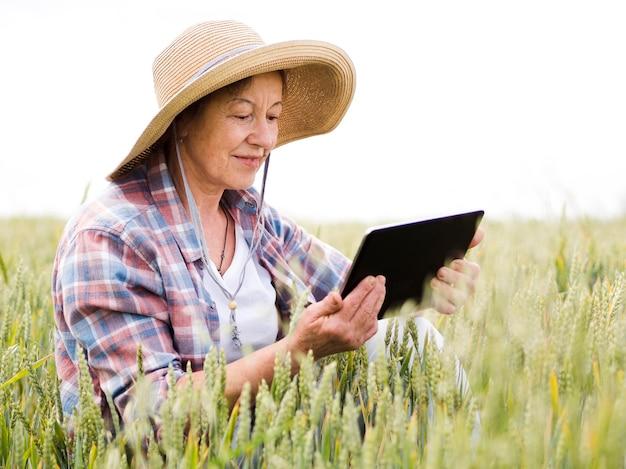 Ältere frau, die auf einem weizenfeld sitzt
