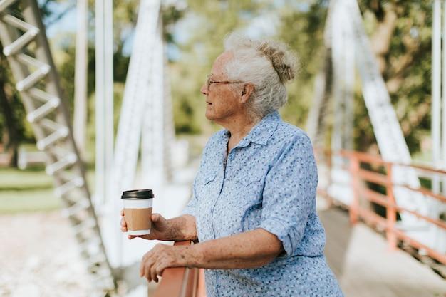 Ältere frau, die auf einer brücke mit einem kaffee steht