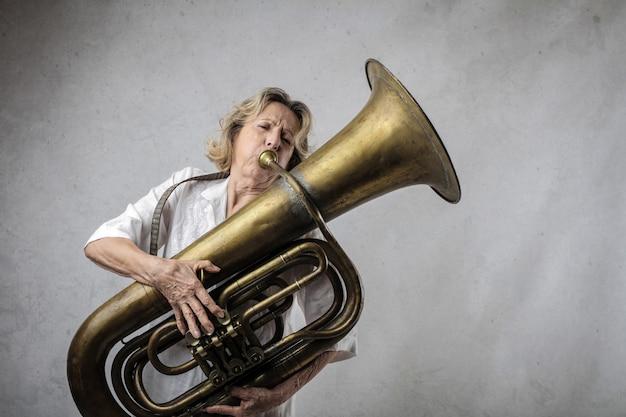 Ältere frau, die auf einer tuba spielt