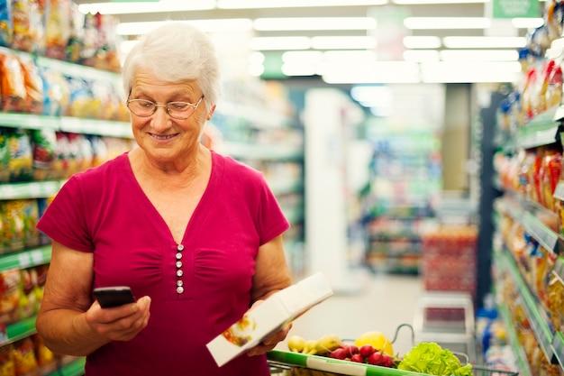 Ältere frau, die auf handy am supermarkt eine sms sendet