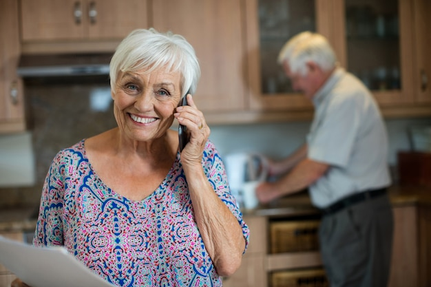 Ältere frau, die auf handy spricht, während mann, der in der küche zu hause arbeitet