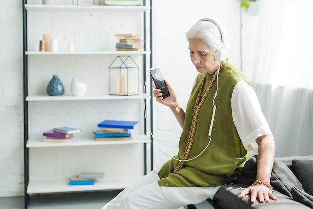 Ältere frau, die auf hörender musik des sofas auf kopfhörer sitzt