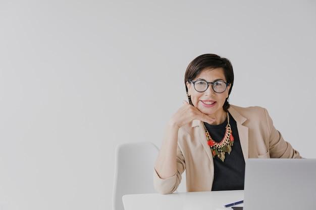 Ältere frau, die auf ihrem büro mit copyspace sitzt