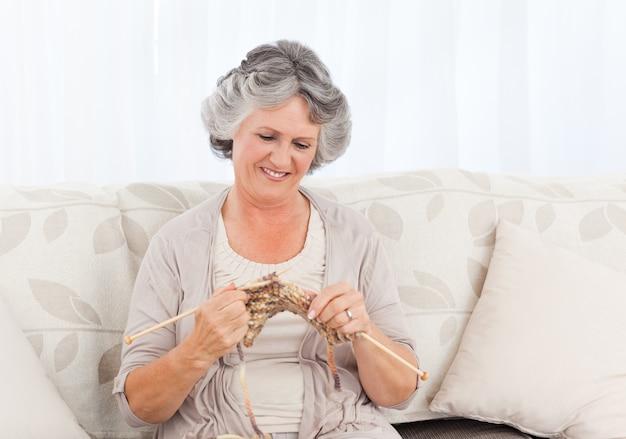 Ältere frau, die auf ihrem sofa strickt