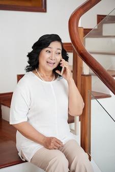 Ältere frau, die auf smartphone spricht
