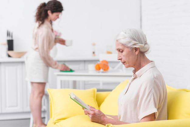 Ältere frau, die auf sofa lesebuch vor frauenreinigungstabelle sitzt