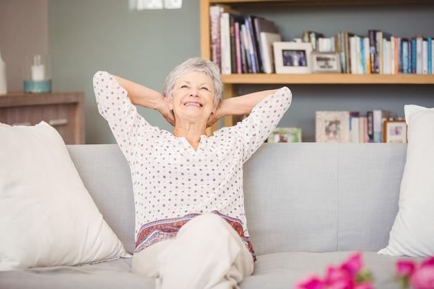Ältere frau, die auf sofa sich entspannt