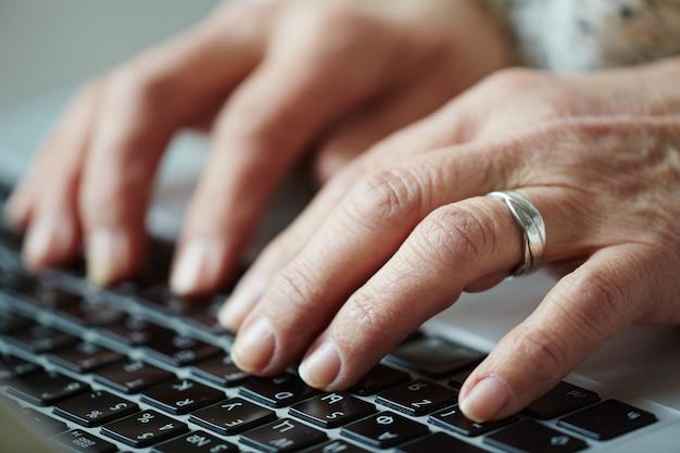 Ältere frau, die auf tastatur schreibt
