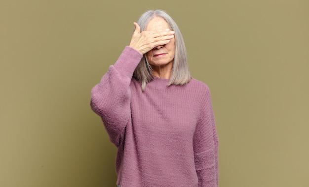 Ältere frau, die augen mit einer hand bedeckt, die sich ängstlich oder ängstlich fühlt, sich wundert oder blind auf eine überraschung wartet