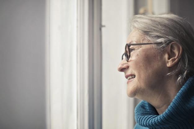Ältere frau, die aus dem fenster heraus schaut
