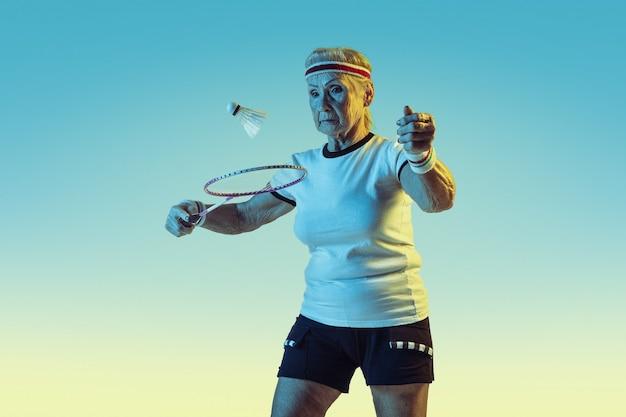 Ältere frau, die badminton in sportbekleidung auf gradientenhintergrund im neonlicht spielt