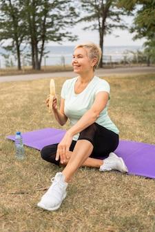 Ältere frau, die banane draußen im park nach yoga isst