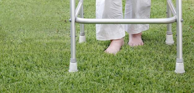 Ältere frau, die barfuß therapie auf gras im hinterhof geht.