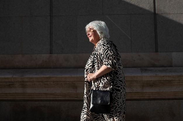 Ältere frau, die bei sonnenuntergang in der stadt geht