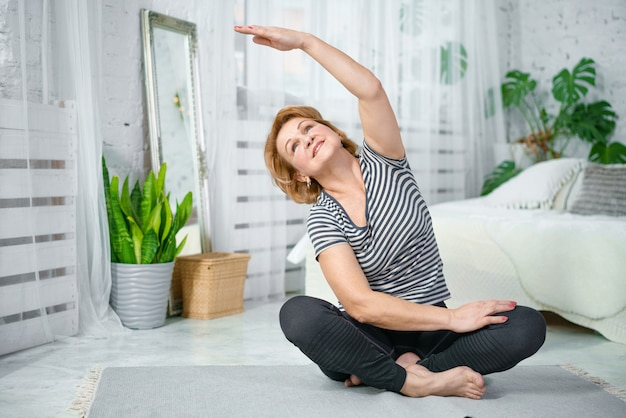 Ältere frau, die beim sitzen in lotussitz trainiert