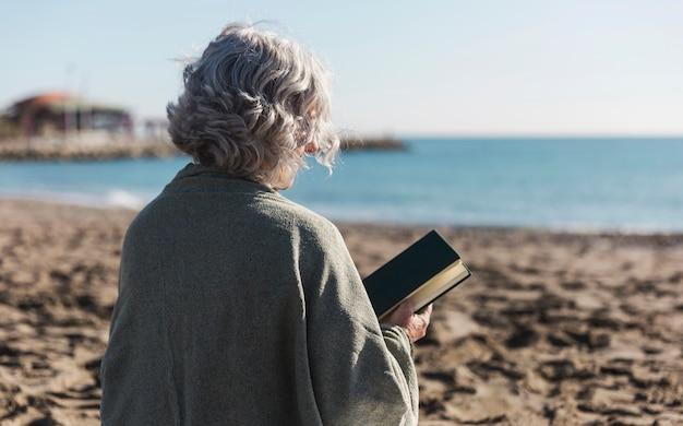 Ältere frau, die buchrückansicht hält