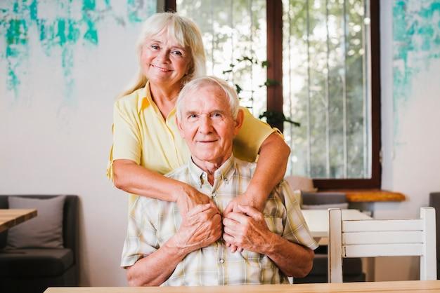 Ältere frau, die den älteren mann zu hause sitzt umfasst