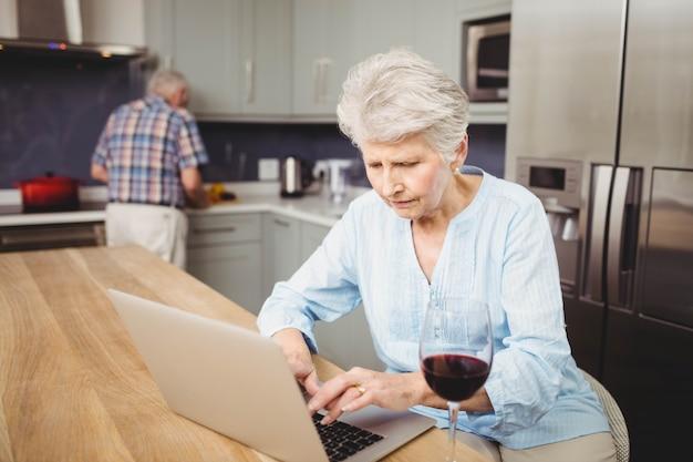 Ältere frau, die den laptop und mann zu hause arbeiten in der küche verwendet