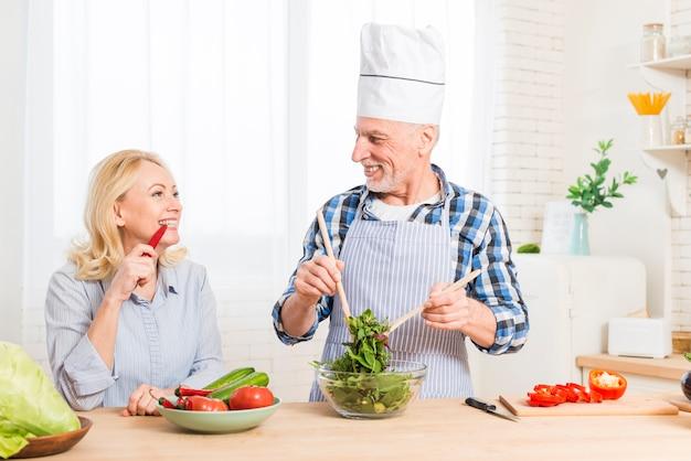 Ältere frau, die den roten paprika beißt, der den salat in der küche zubereitend betrachtet
