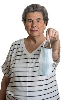 Ältere frau, die der kamera medizinische maske gibt