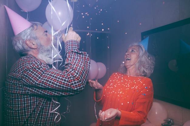 Ältere frau, die die geburtstagsfeier mit ihrem ehemann in der geburtstagsfeier genießt