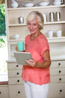 Ältere frau, die digitale tablette beim trinken des kaffees in der küche verwendet