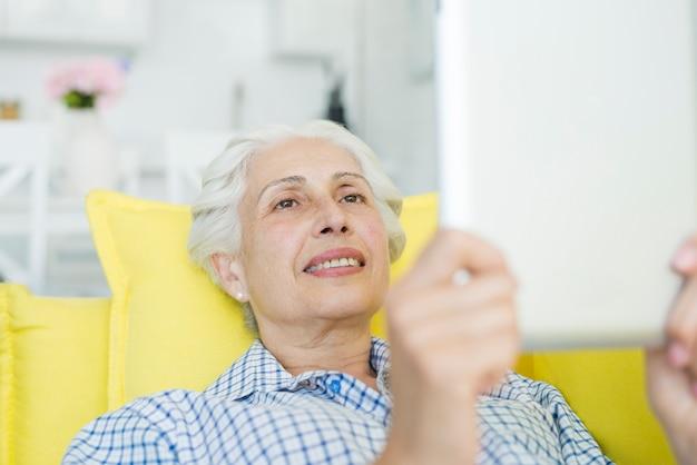 Ältere frau, die digitale tablette betrachtet