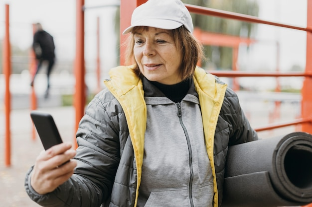 Ältere frau, die draußen arbeitet, während sie smartphone und matte hält