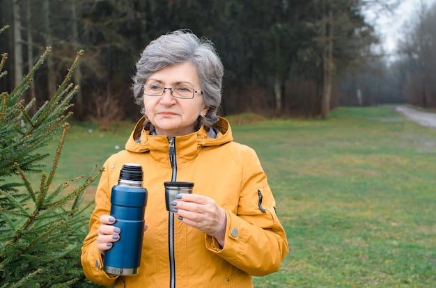 Ältere frau, die draußen im wald geht. ältere frau, die thermoskanne und tasse heißen tee hält. konzeptwanderung, wärmendes getränk bei kaltem wetter.