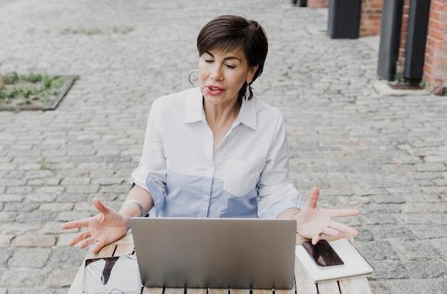 Ältere frau, die draußen mit dem laptop sitzt