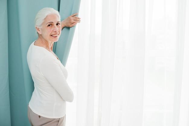 Ältere frau, die durch das fenster schaut