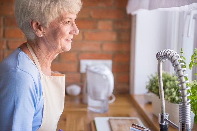 Ältere frau, die durch das küchenfenster schaut