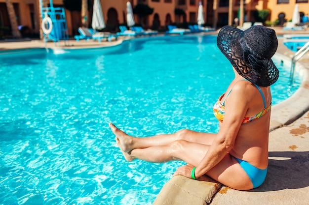 Ältere frau, die durch hotelswimmingpool sich entspannt.