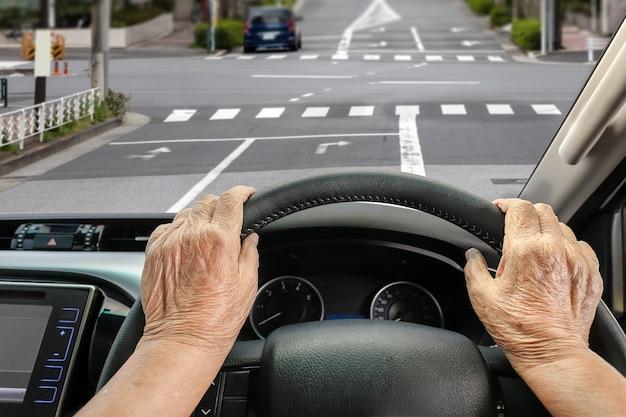 Ältere frau, die ein auto auf der straße in der stadt fährt.