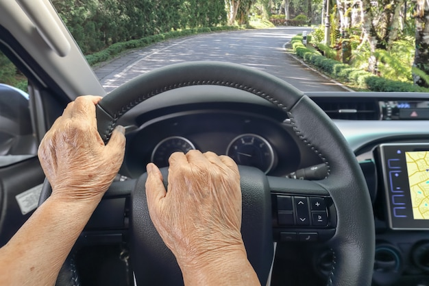 Ältere frau, die ein auto fährt